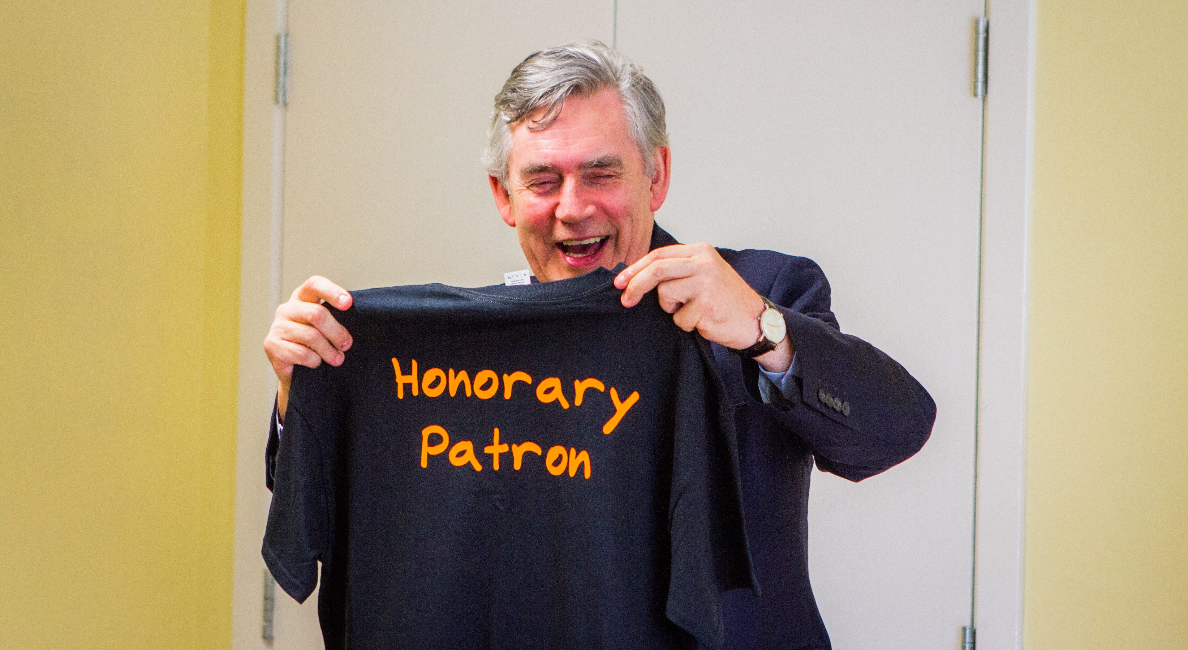 Gordon Brown with a T-shirt that was presented to him as a gift.