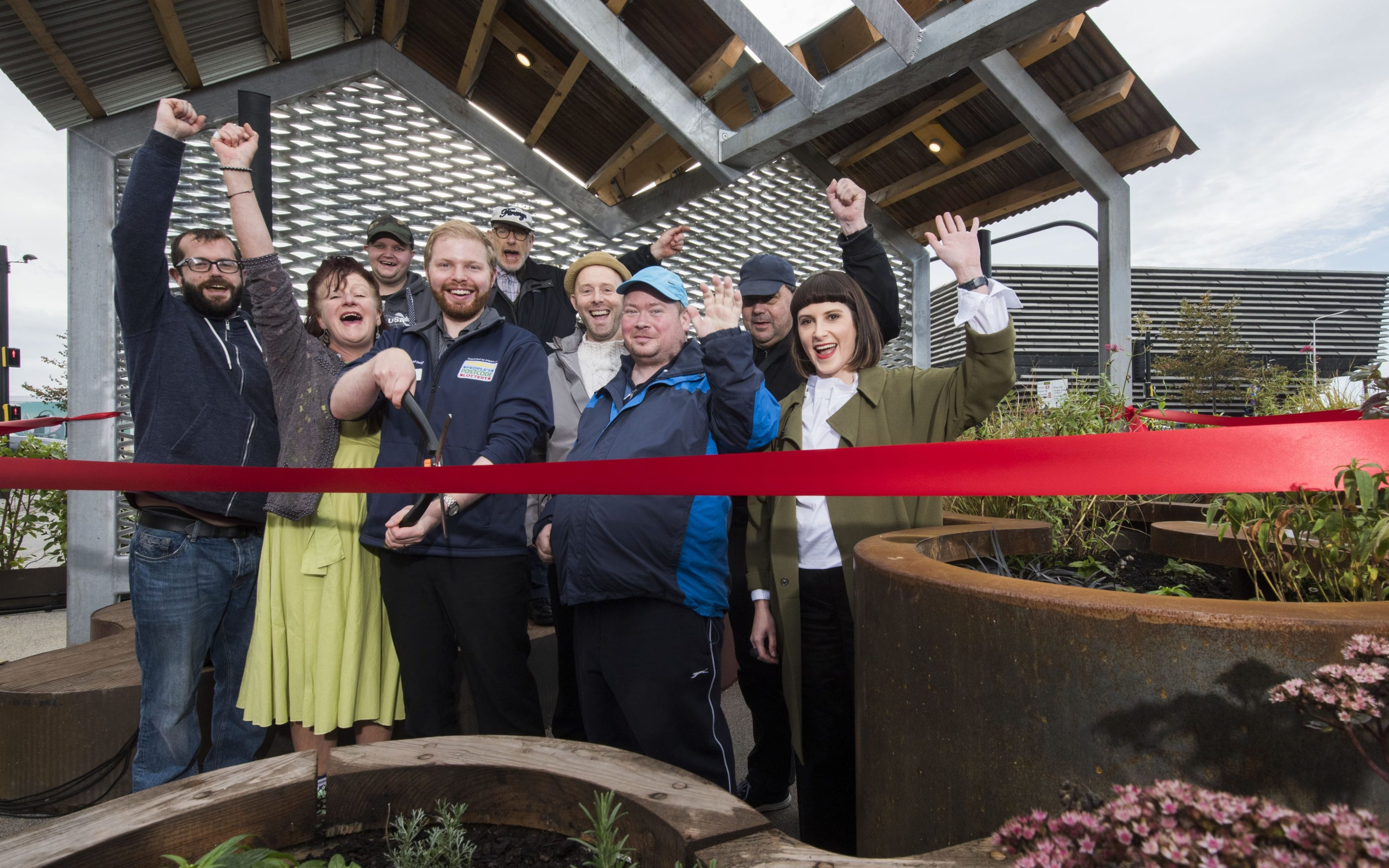 The design team and volunteers cutting the ribbon at the unveiling of the V&A community garden.