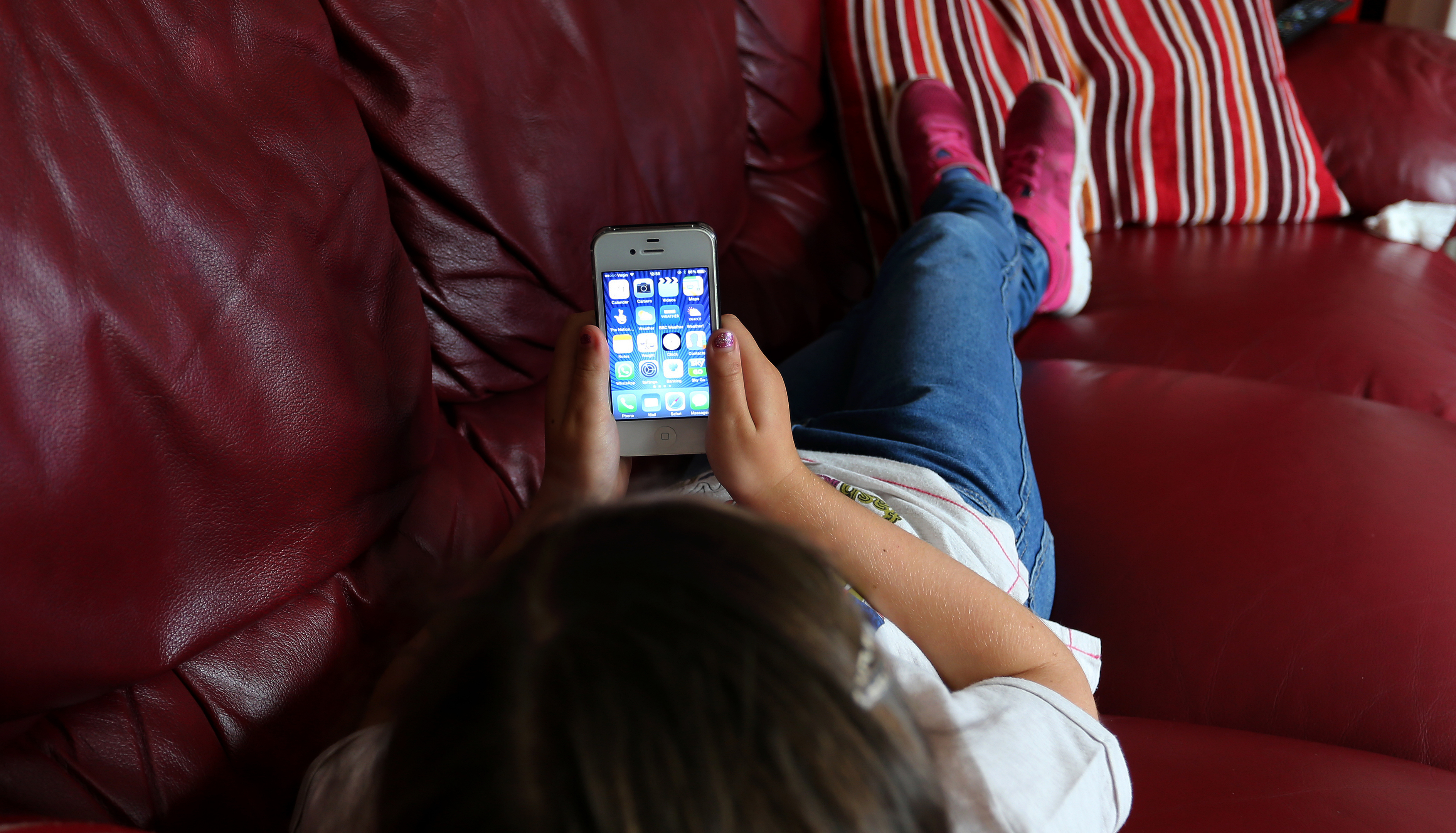 A child using an Apple iPhone smartphone.
