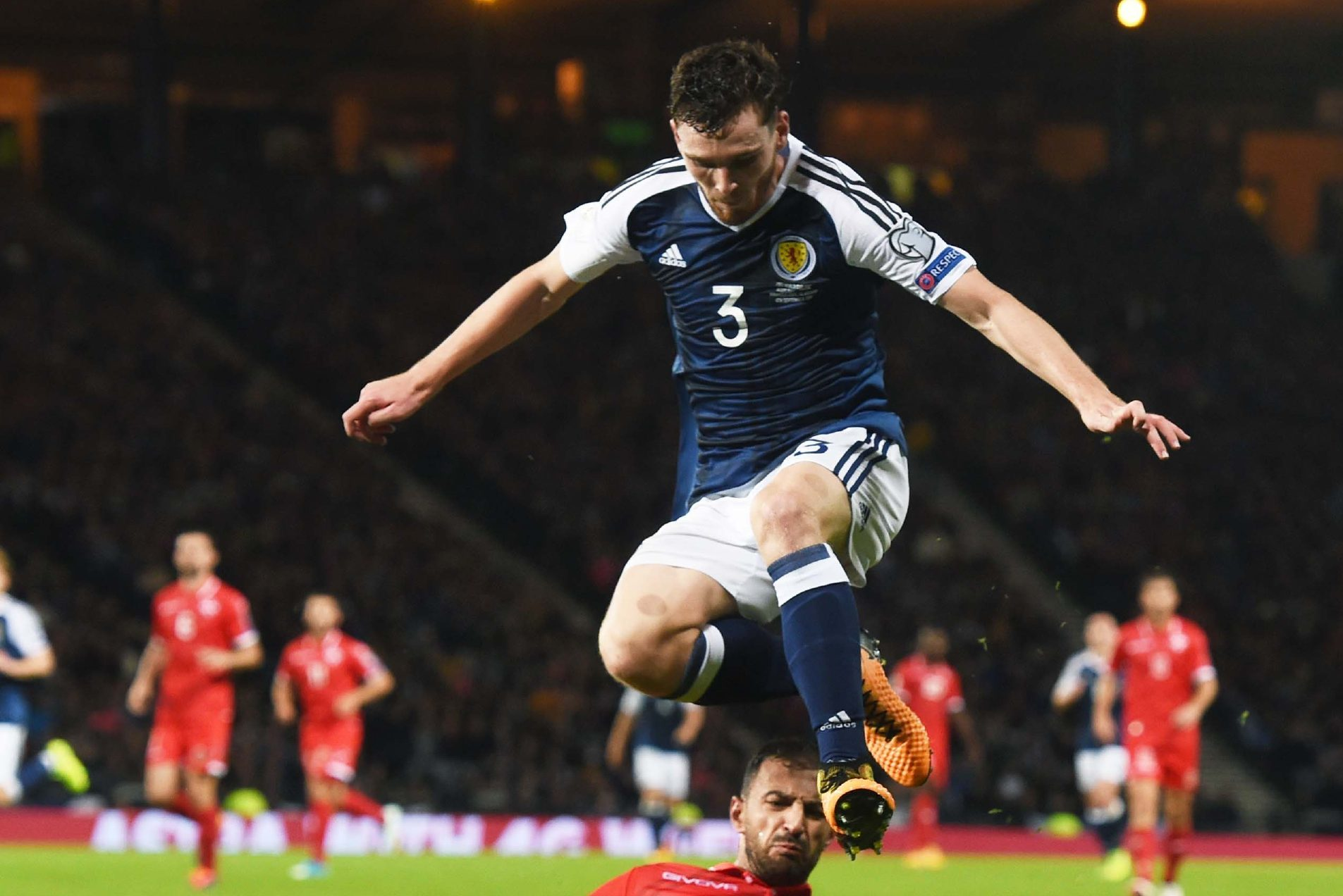 Scotland's Andrew Robertson jumps over a challenge by Malta's Steve Borg.