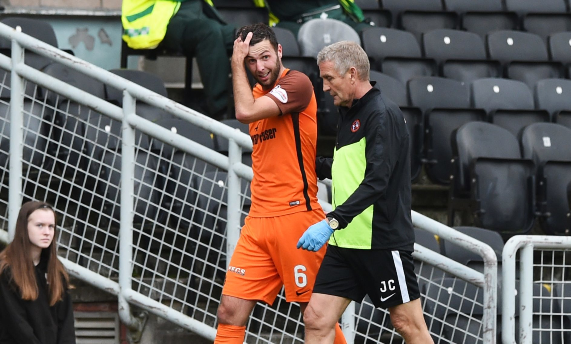 Lewis Toshney walks off with physio Jeff Clarke after hurting his ankle.