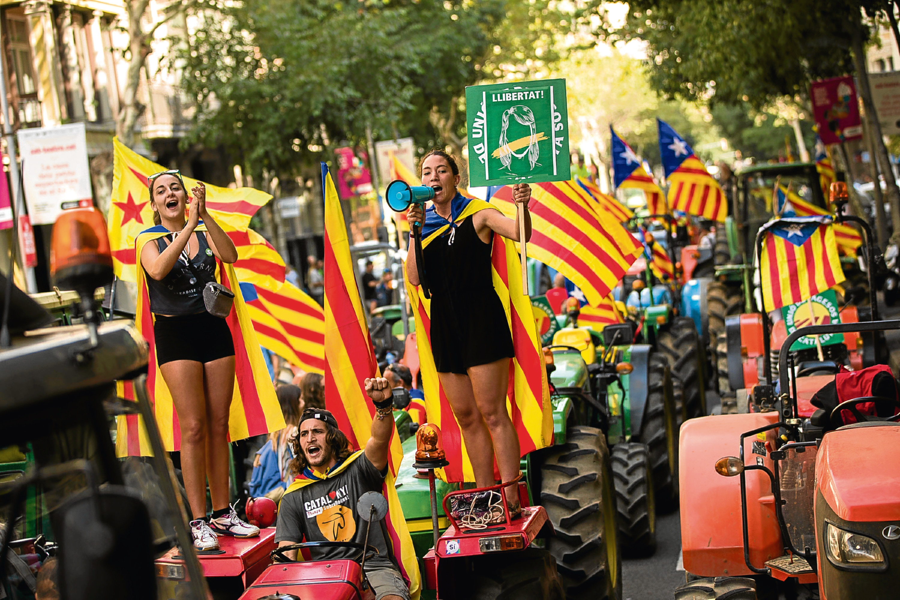 People with the estelada, or independence flags, shout slogans on top of parked tractors during a protest by farmers in Barcelona.