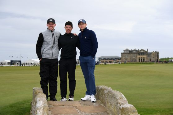 Connor Syme, Rory McIlroy and One Direction's Niall Horan pose for photos on the Swilcan Bridge yesterday.