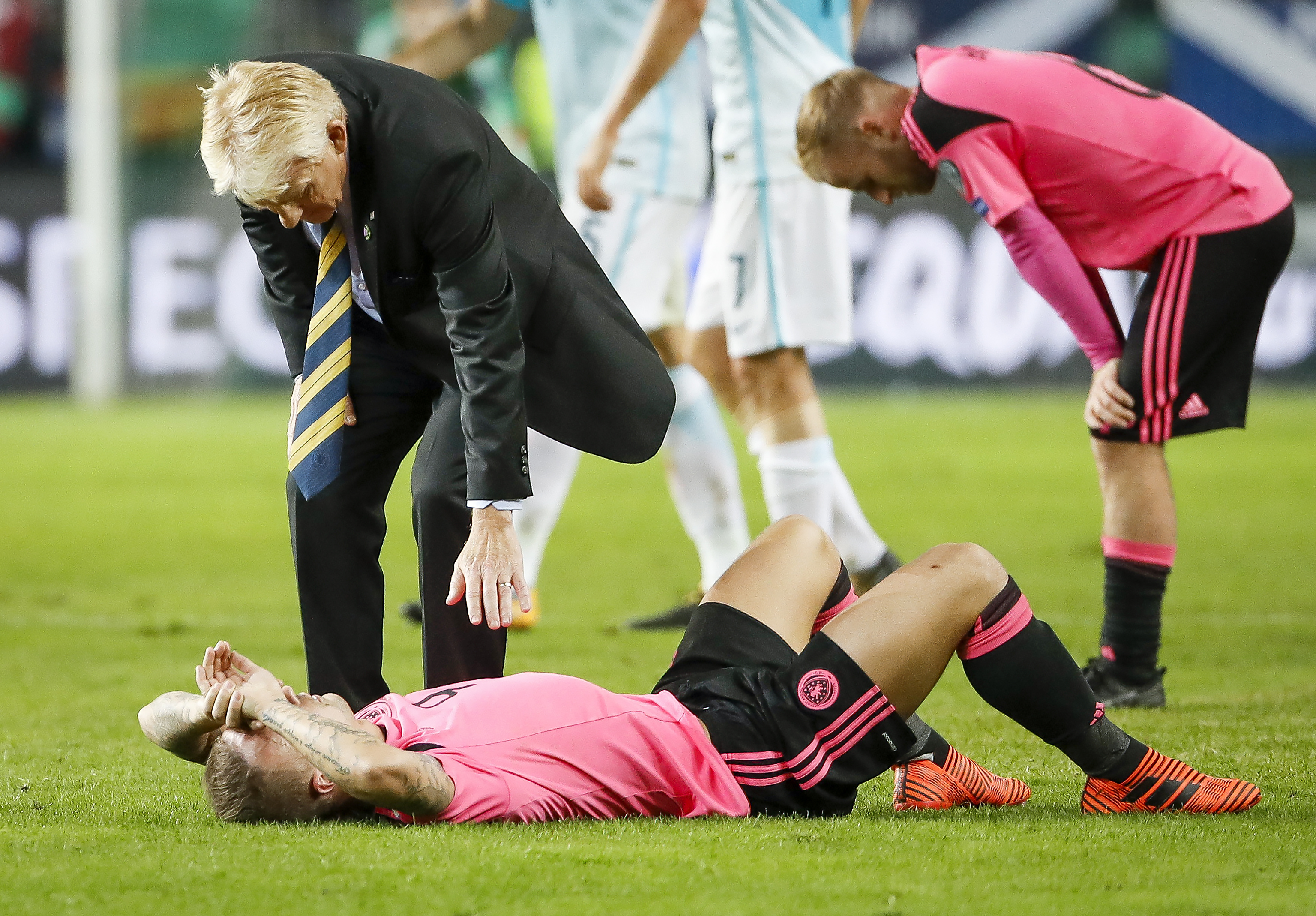 Head coach Gordon Strachan (top) comforts Leigh Griffiths of Scotland after the FIFA 2018 World Cup Qualifier match between Slovenia and Scotland
