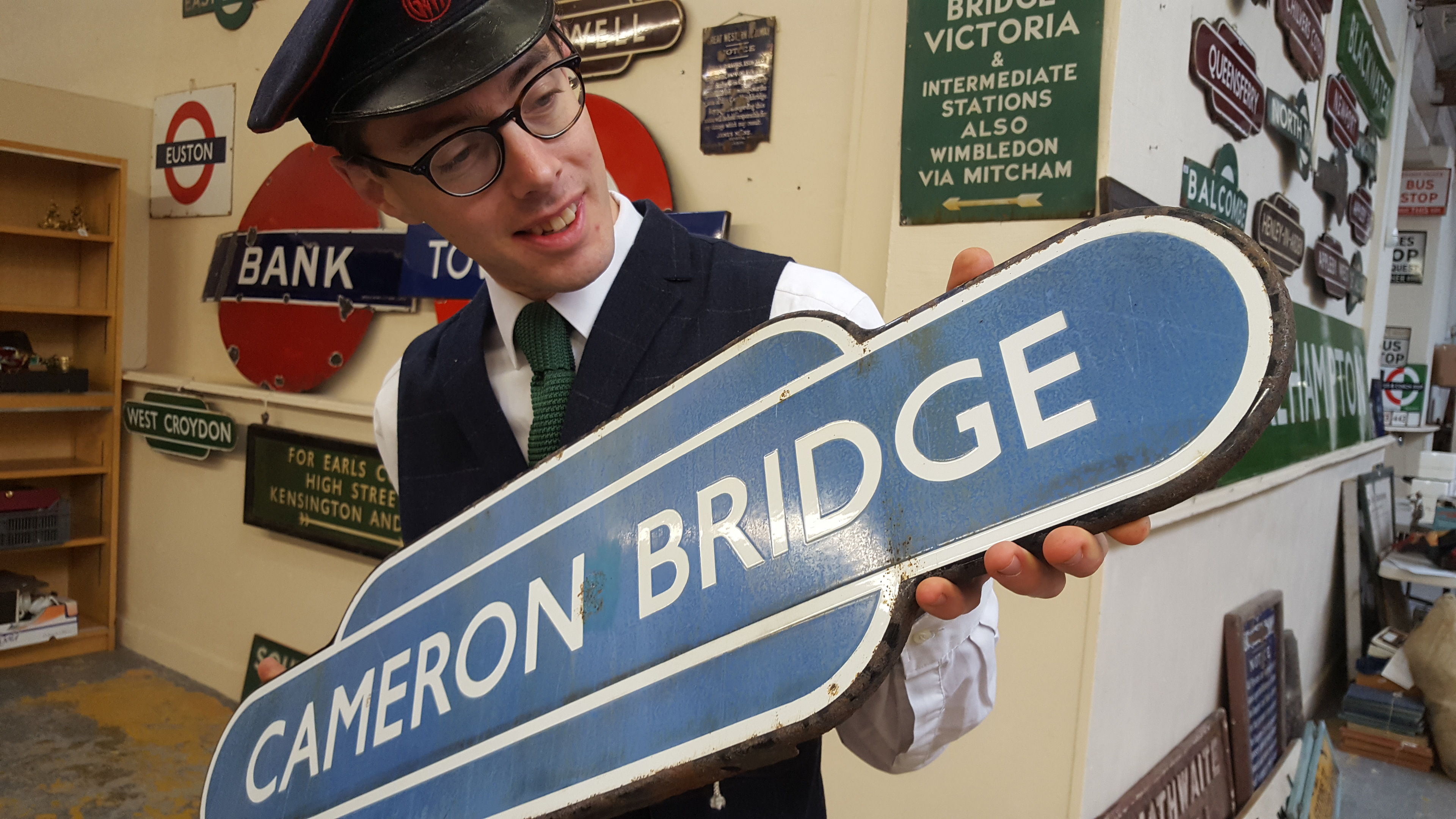 Auctioneer Richard Edmonds with the Cameron Bridge sign.