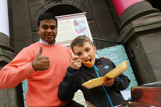Praveen Kumar with Josh Ferris tucking into his curry, as part of World Food Day in Perth.
