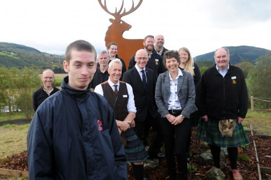 Aberfeldy youngster Bailey Pearce who works at The Workshop and helped design the piece with Highland Safaris staff, John Swinney MSP and the stag sculpture.