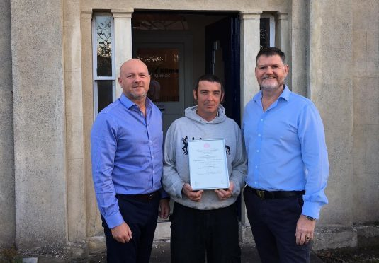 Neil Reilly receives the Royal Humane Society Resuscitation Certificate from Kilmac director Richard Kilcullen (left) and Athole McDonald.