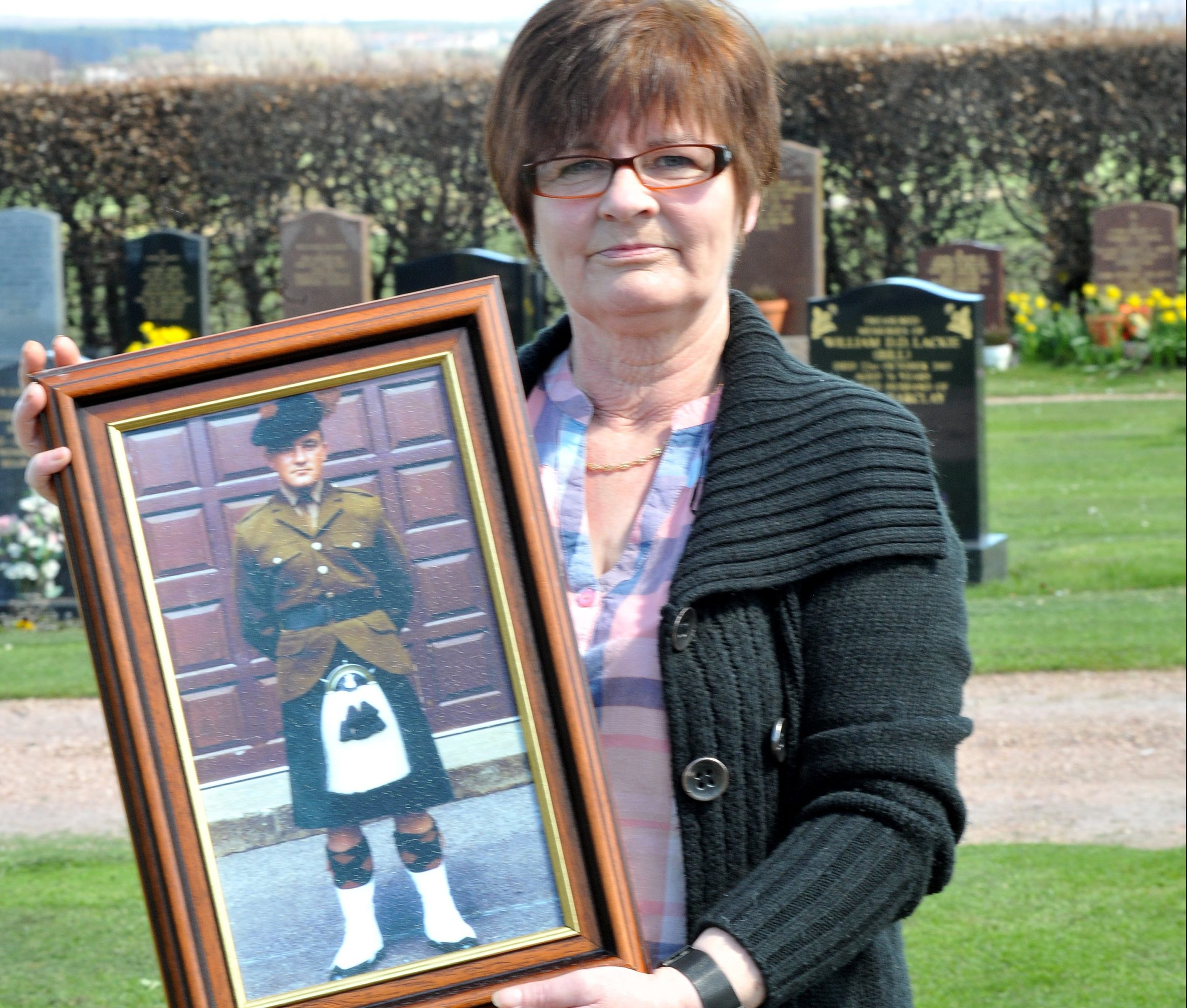 Catherine Kinnear holds a picture of her son at Falkland Cemetery where he is buried.