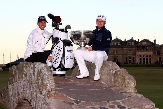 Tyrrell Hatton of England holds the trophy aloft with his caddie Chris Rice on the Swilken Bridge on the 18th hole after winning the Alfred Dunhill Links Championship at The Old Course last year.