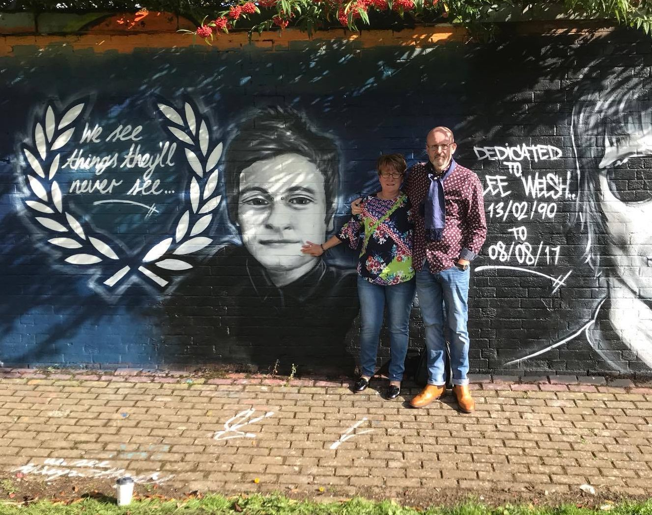 Lee's parents Phil and Lesley with a mural dedicated to their son.