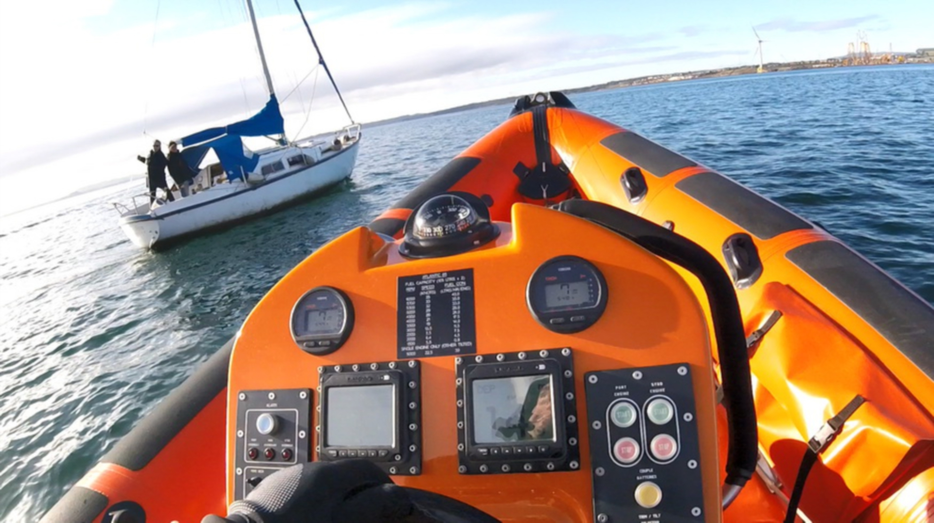 The crew pull alongside with the sailing vessel transmitting the distress signal.
