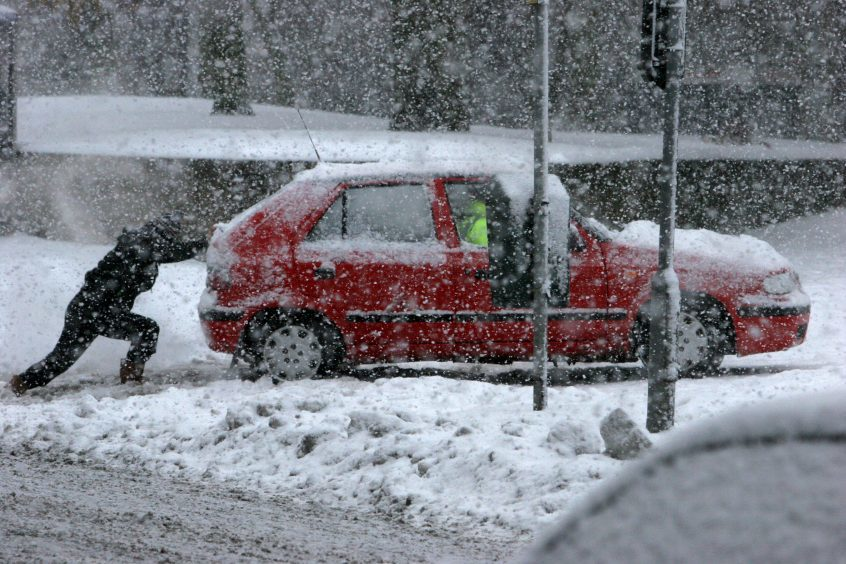 A man pushes a car through snow in Dundee, 2010.