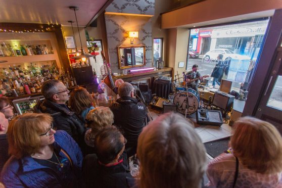 Musician Mike Whelans entertains a packed out Bruach bar on Brook Street.