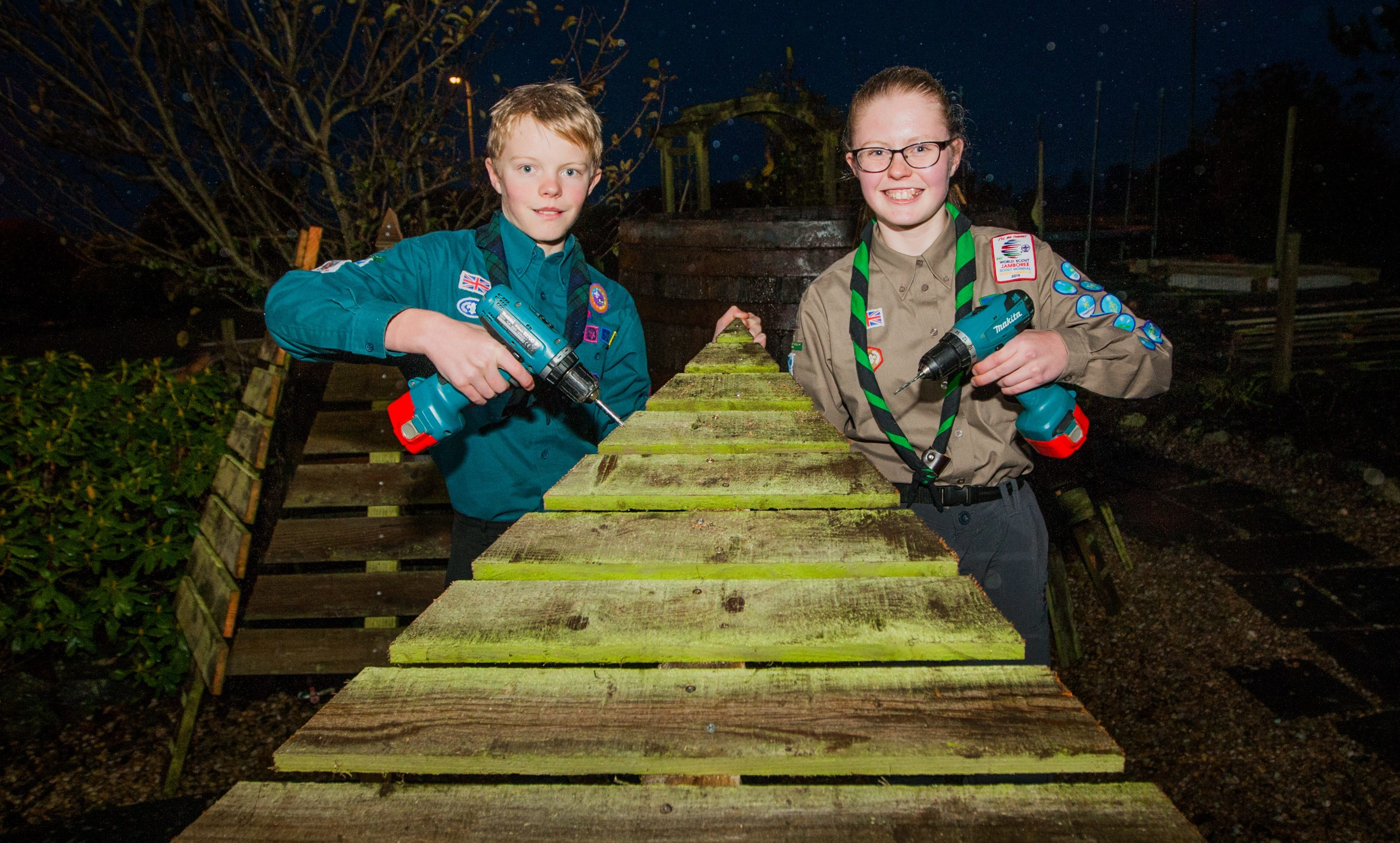 Fundraising Scout Ailsa Bennet upcycling old fence wood into Christmas Trees to raise money for trip South America, with brother Struan Bennet.
