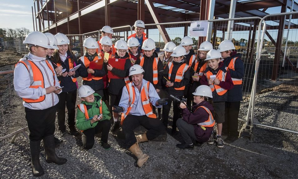 Site manager Stuart Giles with the young reporters. Sixteen pupils from eight local primary schools (two from each) visited the site of the new Bertha Park High School – part of the new Bertha Park Village on the outskirts of Perth.