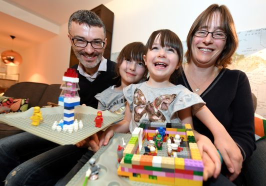 Nick and Susan Woollacott with their daughters Heather (left) and her sister Izzy with a rocket and noodle restaurant made out of Lego.