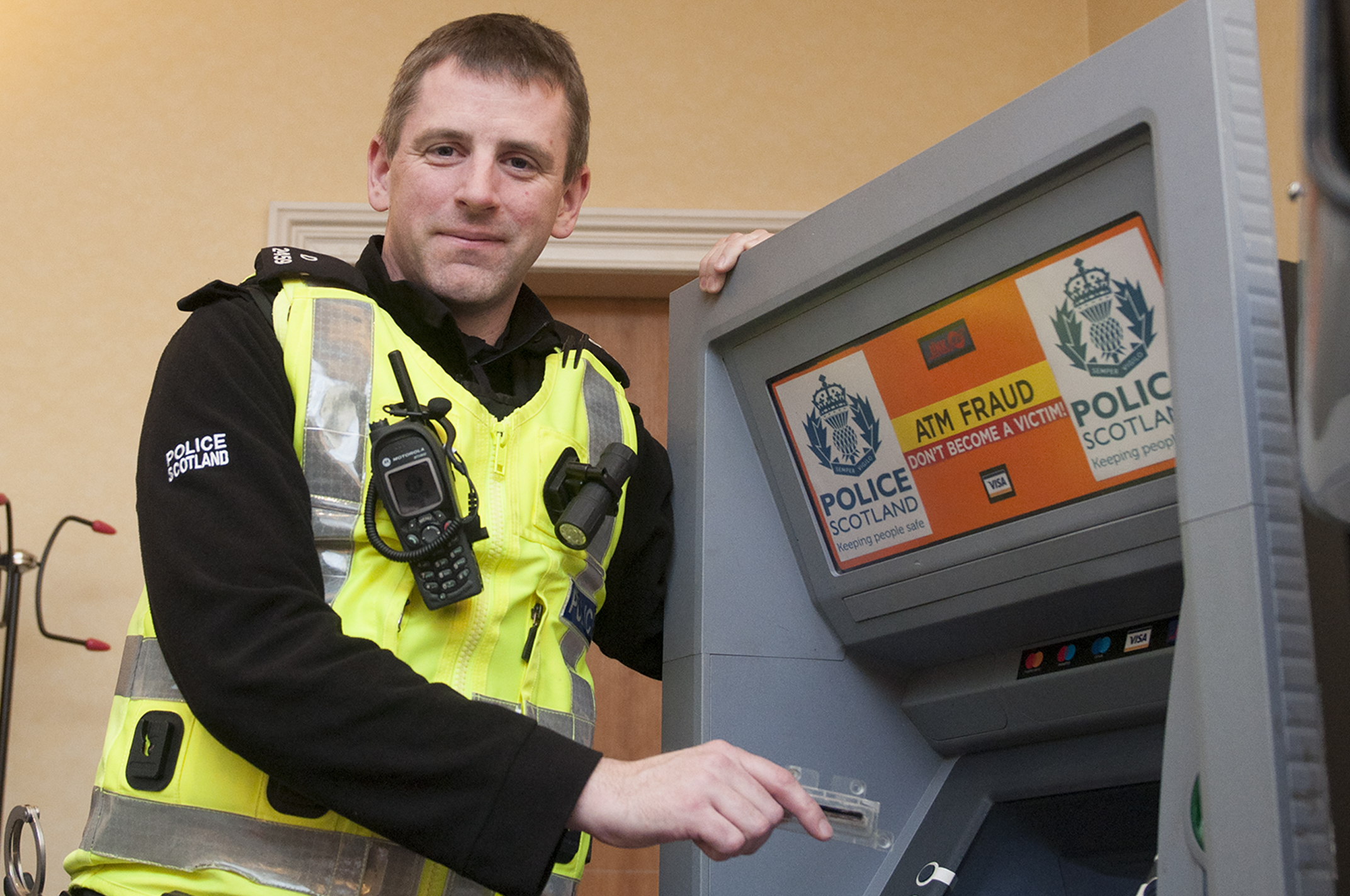 Community police officer, Scott Anderson, demonstrates ATM scams at the pop-up event