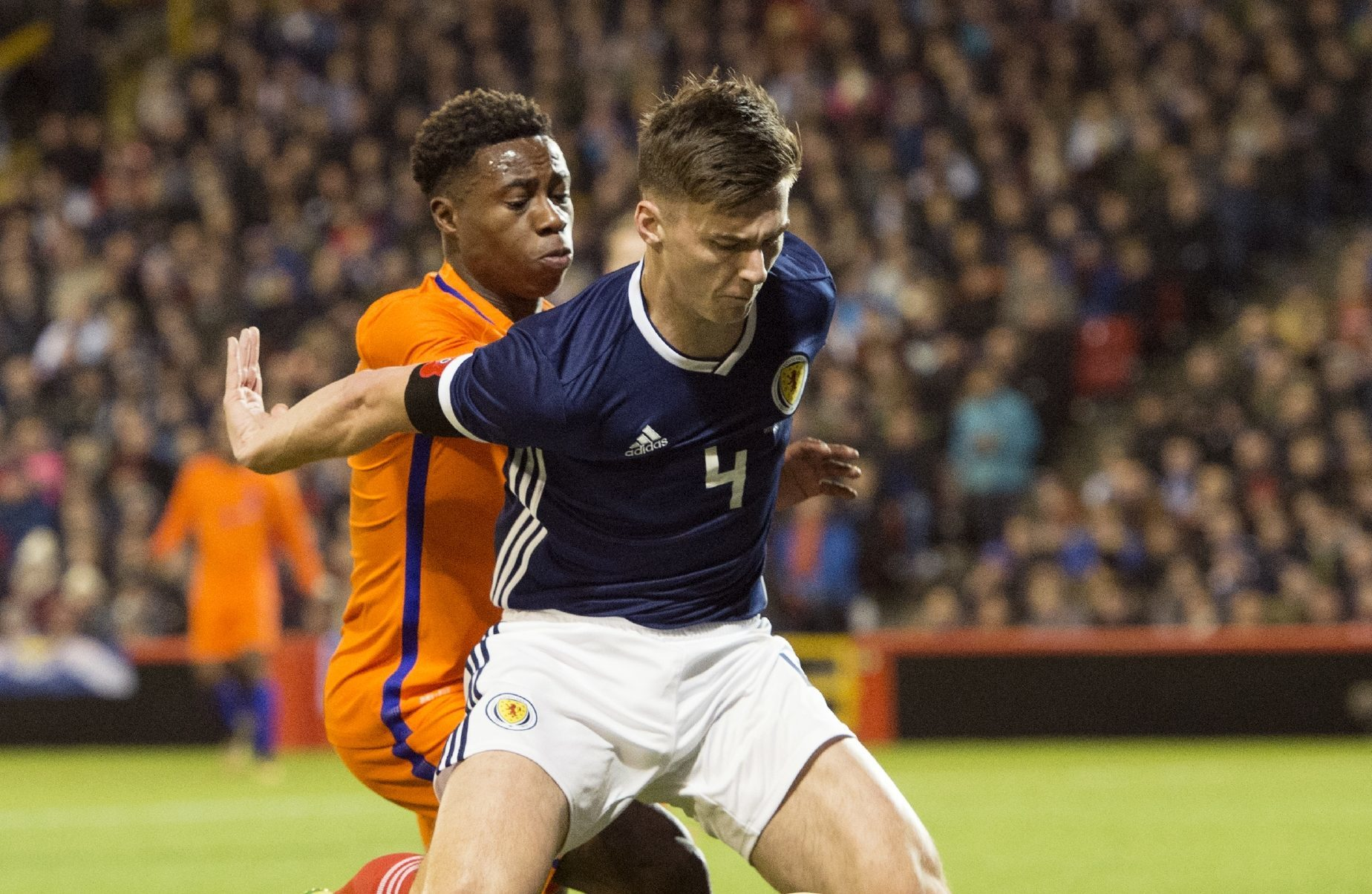 Kieran Tierney holds off Holland player Quincy Promes.