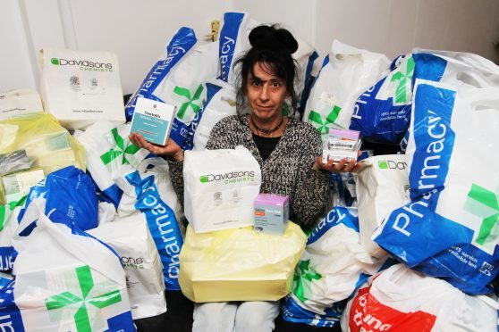 Jane Mclean with the prescription drugs she found in the attic of her new home.