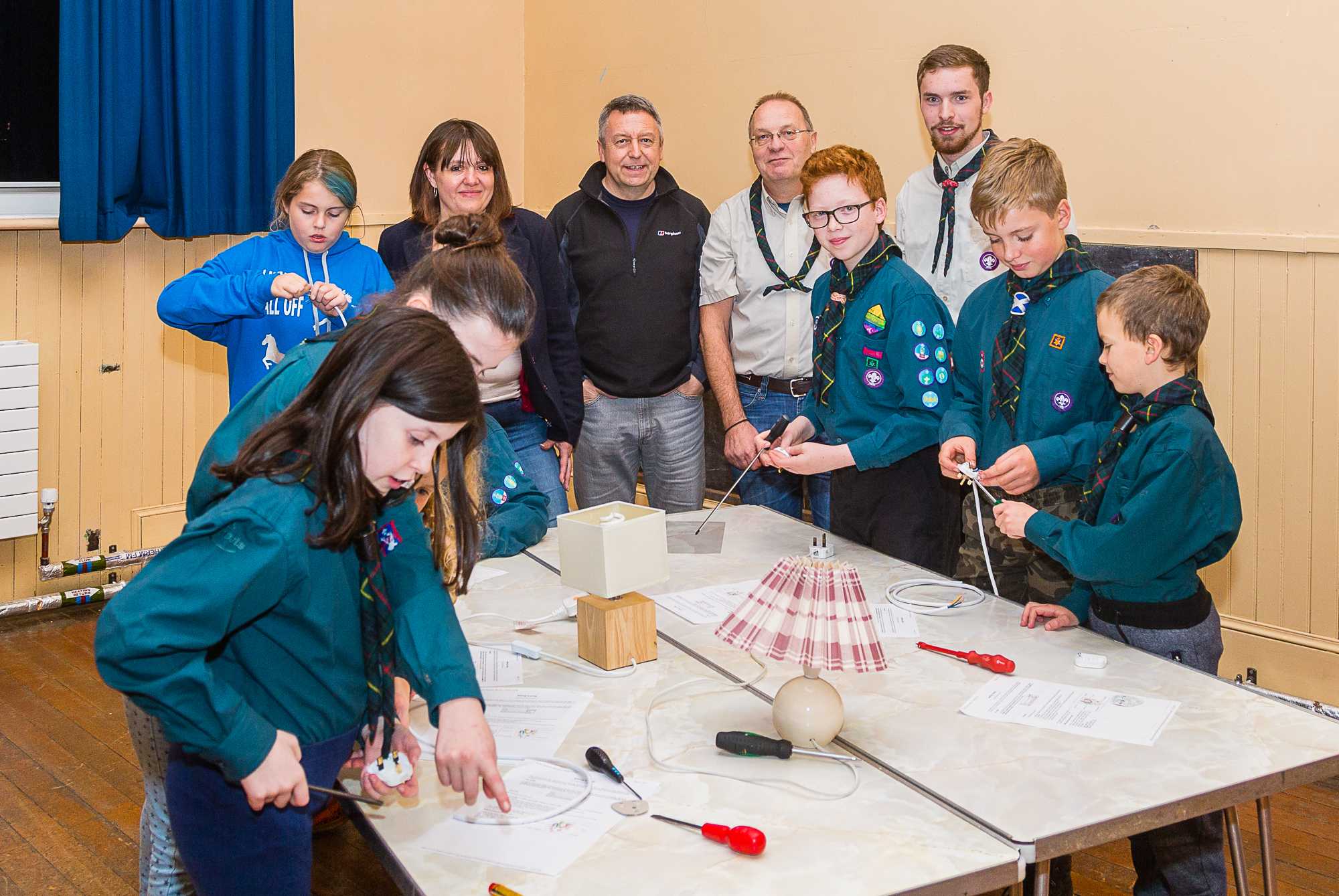 Councillor Angus Forbes with Scout Leaders Richard Prince and Cameron Peach and young Scouts in the community hall.
