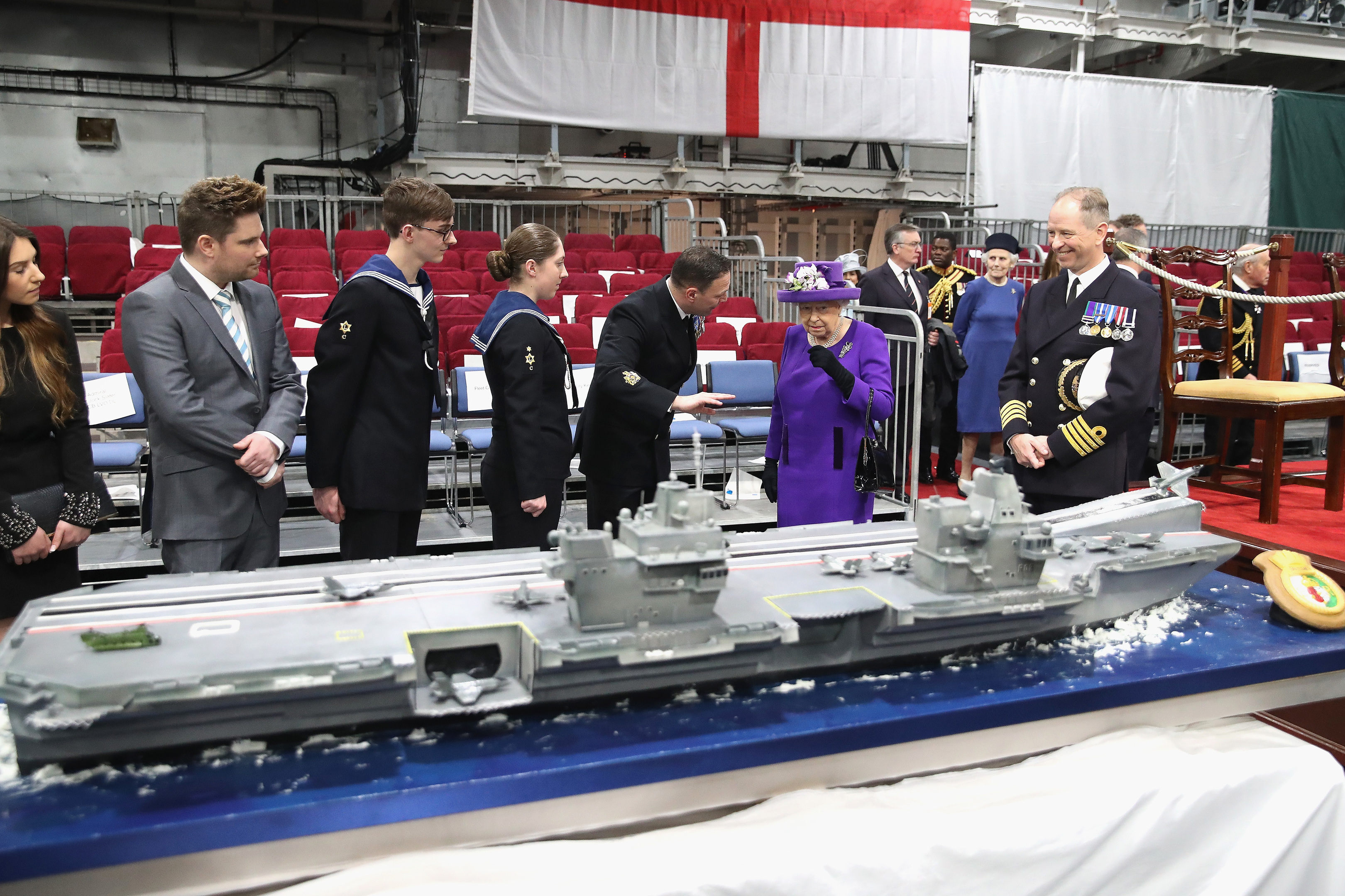 Queen Elizabeth II  looks at a cake made by David Duncan during the Commissioning Ceremony of HMS Queen Elizabeth at HM Naval Base