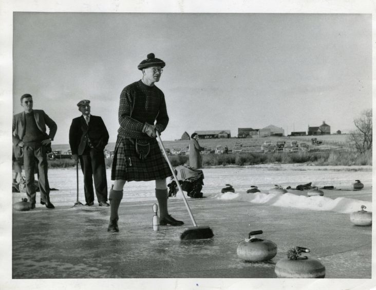 Kilted George Doig, Southesk, in play at the Dun's Dish Bonspiel. January 1963.