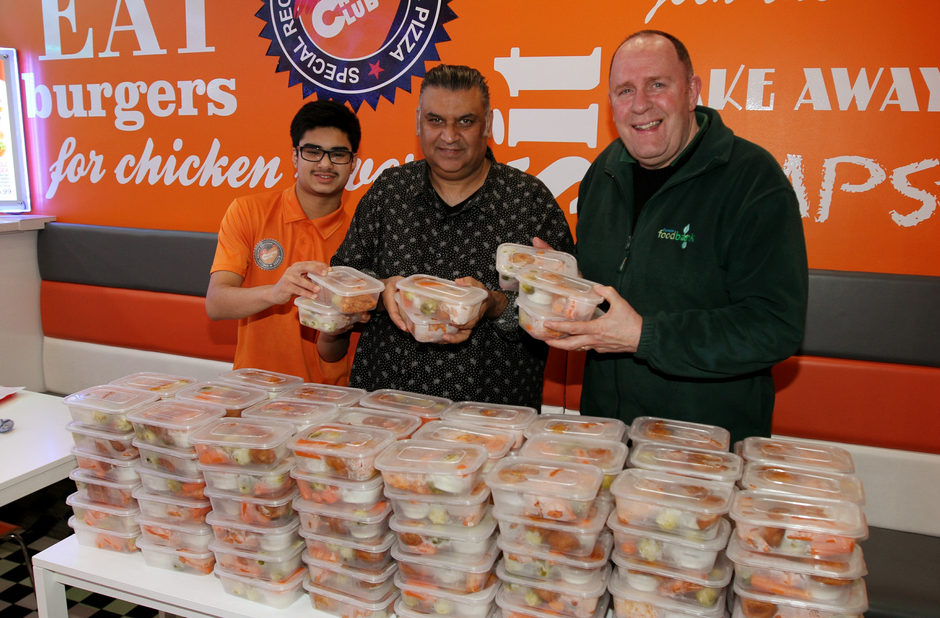 Ken Linton (right) of the Dundee Foodbank accepts meals from Daud Sheikh and Ibrar Ibrahim of the Chicken Club.