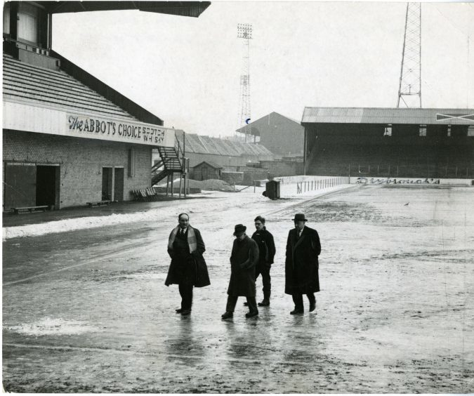 Photograph showing Jerry Kerr (manager), Ernie Robertson (chairman), Albert Lorimer (groundsman), Johnstone Grant (director) walking along an ice covered Tannadice Park. January 1963.