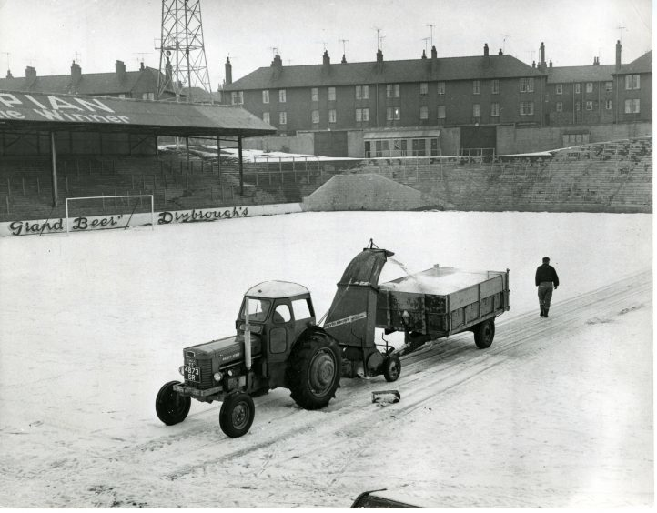 Photograph showing the groundskeepers as they use a snow blower to clear the snow from the grounds at Tannadice Park. 20 February 1963.