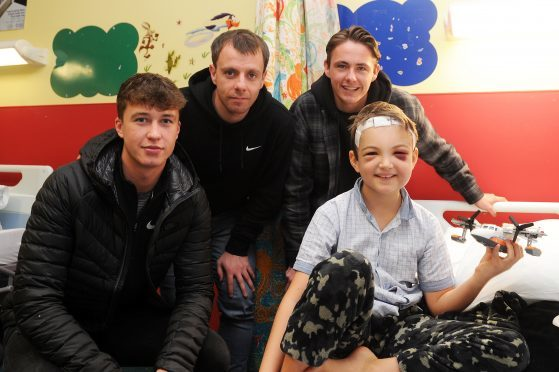 Jack Hendry, Paul McGowan and Scott Allan visiting nine-year-old Marcus Summers.