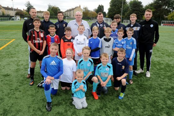 Fair City FC and Letham FC football clubs came together in October 2016. One year on, they are to go their separate ways once more. Pictured as the merger was announced are  youngsters and coaches from each of the clubs with Letham's then president Ken Drummond (who sadly died this year) and Secretary Jon Kidd.