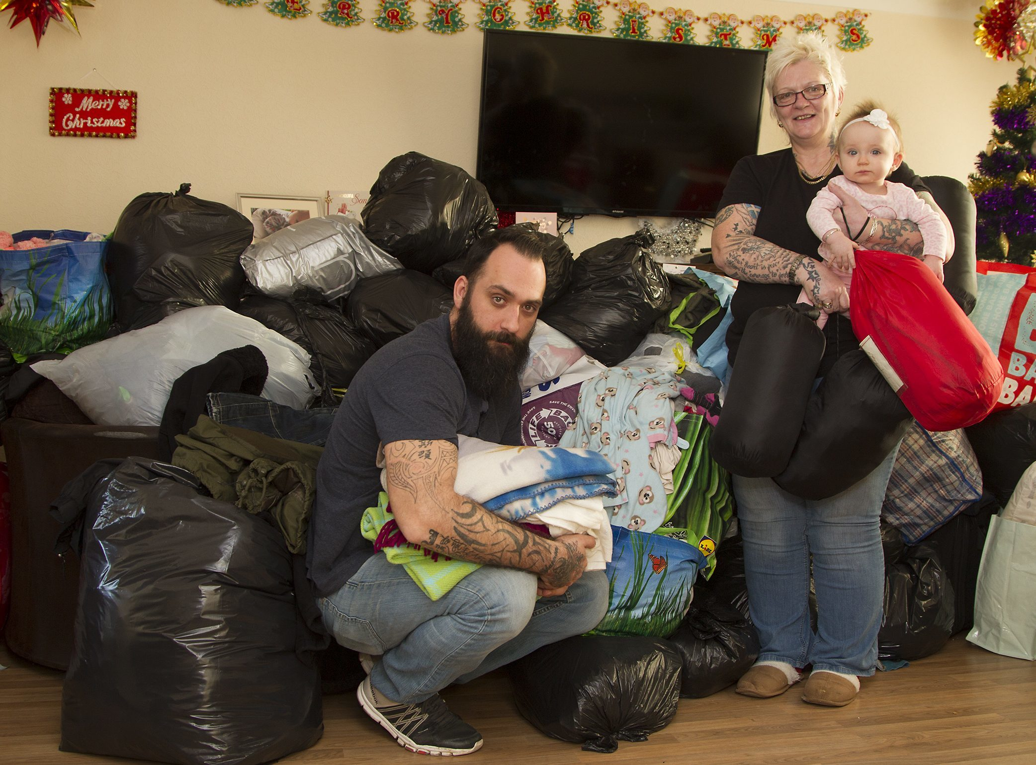 Christian with his daughter Elizabeth and his mum Lesley Whittet with mountains of donated gifts that he plans to distribute on Saturday.