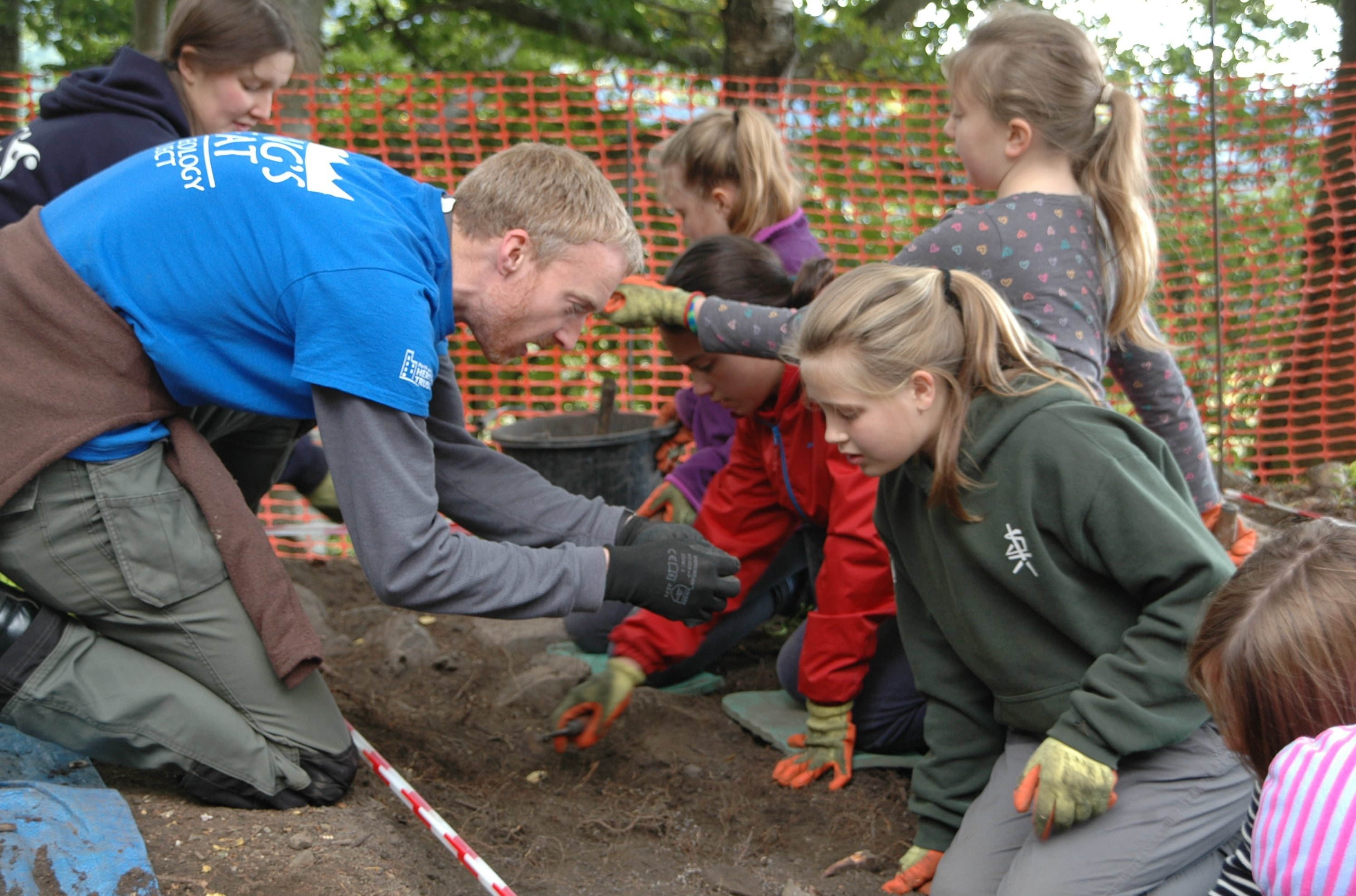 PKHT outreach officer Gavin Lindsay and AOC Archaeologist Katie Roper teaching P6 pupils from Royal School of Dunkeld how to dig and identify artefacts at the fort.
