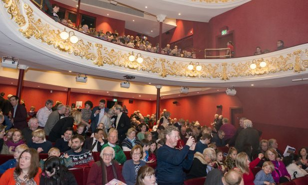 Members of the audience gather for the first performance inside the renovated theatre.