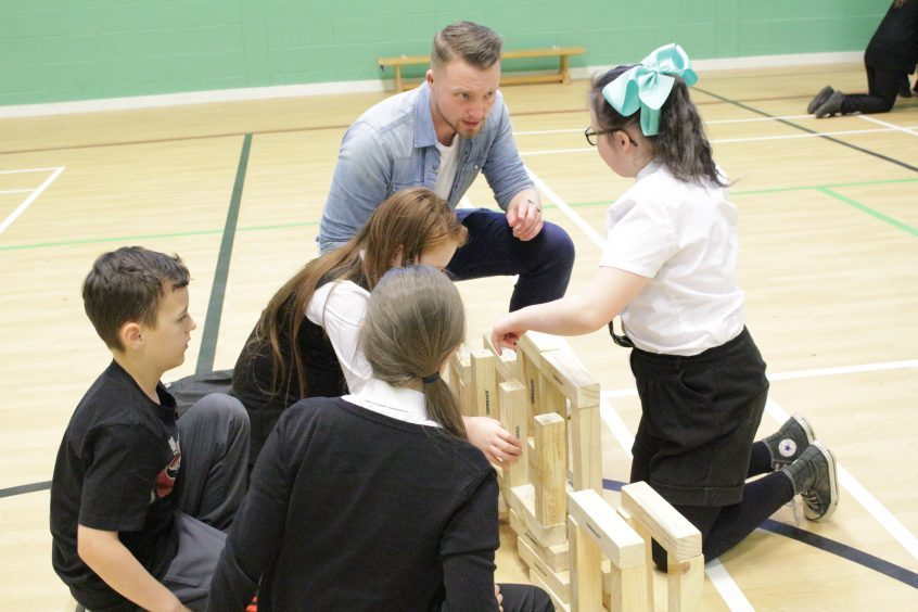 RAE4: Abertay 4th Year Civil Engineering student Stephen Brindle helps St Peter and Paul's Primary School children construct an archway using giant jenga blocks during Fife Science Festival at Craigowl PS.
