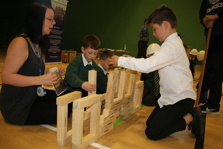 Children from Craigowl Primary School construct an archway using giant jenga blocks during Fife Science Festival.