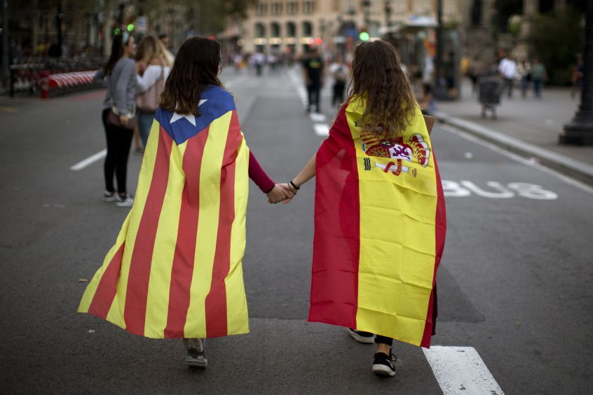 Irene Guszman, 15, wearing a Spanish flag and Mariona Esteve, 14, wearing an estelada or independence flag, walk along the street to take part at a demonstration in Barcelona, Spain.