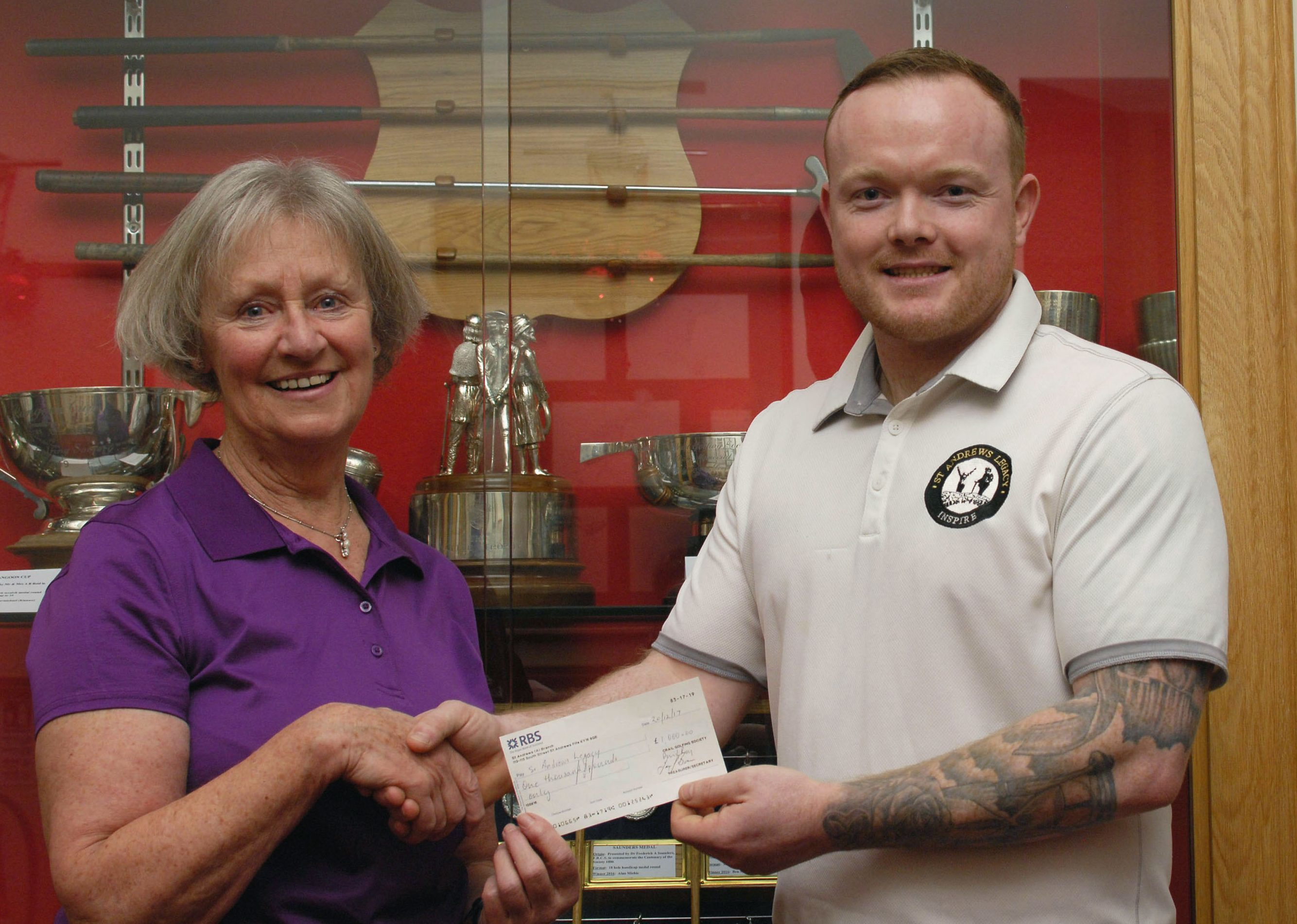 Pam Smith, captain of Crail Golfing Society, presents a cheque for £1000 to David Gillies, representing St Andrews Legacy, a charity that helps ill and injured military veterans towards recovery through golf.
