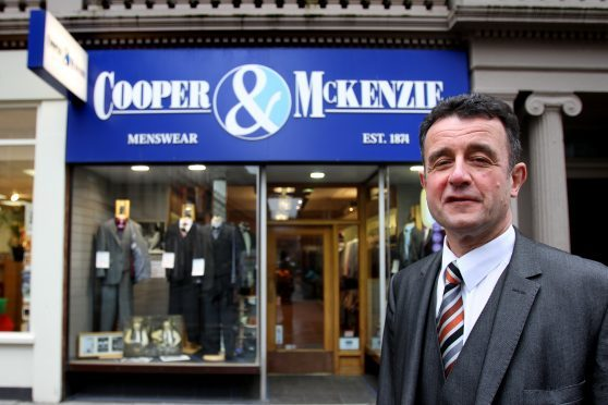 Grant Mitchell outside Cooper and McKenzie to celebrate its 140th anniversary in 2014.