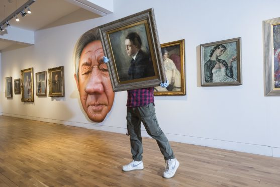 A worker carries an image for installation ahead of the opening of the double portraits exhibitions, Revealing Character and Face to Face, at the McManus in Dundee. Picture: Alan Richardson