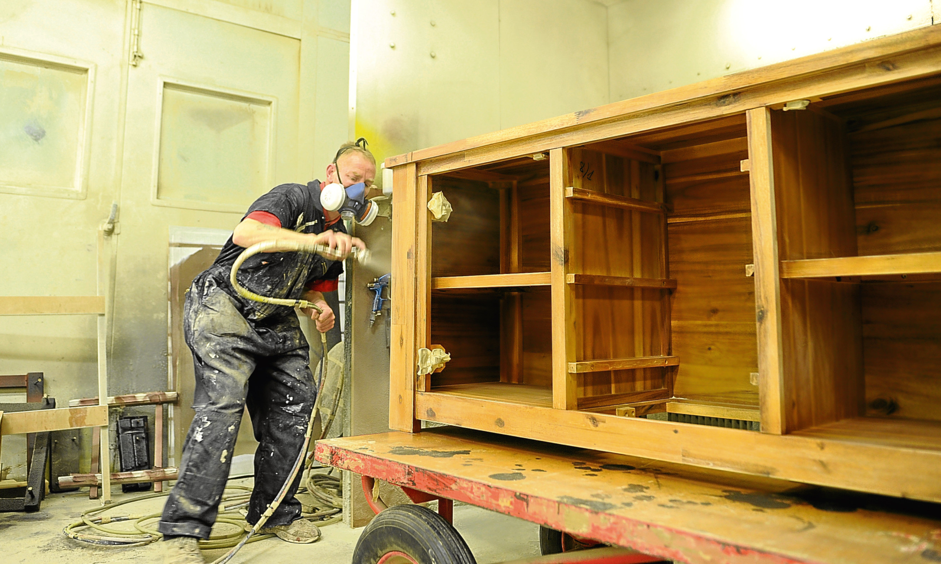 A worker puts the finishing touches to a sideboard unit at Dovetails base at Dunsinane industrial Estate.
