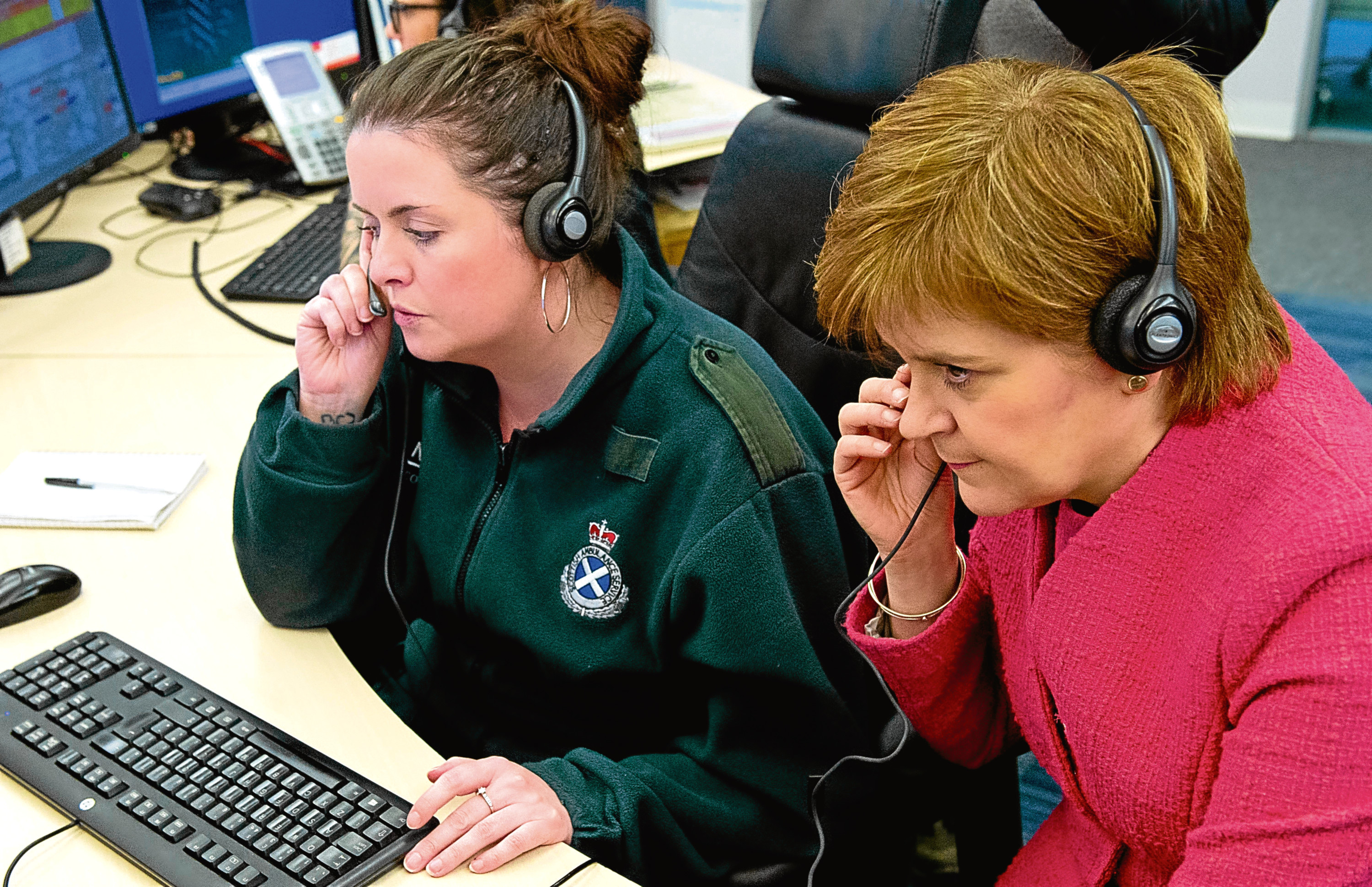 First Minister Nicola Sturgeon listens into a 999 call with Avril as she tours call centre and meets Scottish Ambulance Service call handlers, and NHS 24 staff in Cardonald Glasgow.
