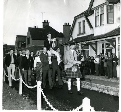 Monifieth club member Willie Black pipes Ian Hutcheon along the front of the other Monifieth clubs on his way to the clubhouse, where the celebrations took place after he won the amateur championship in 1973.