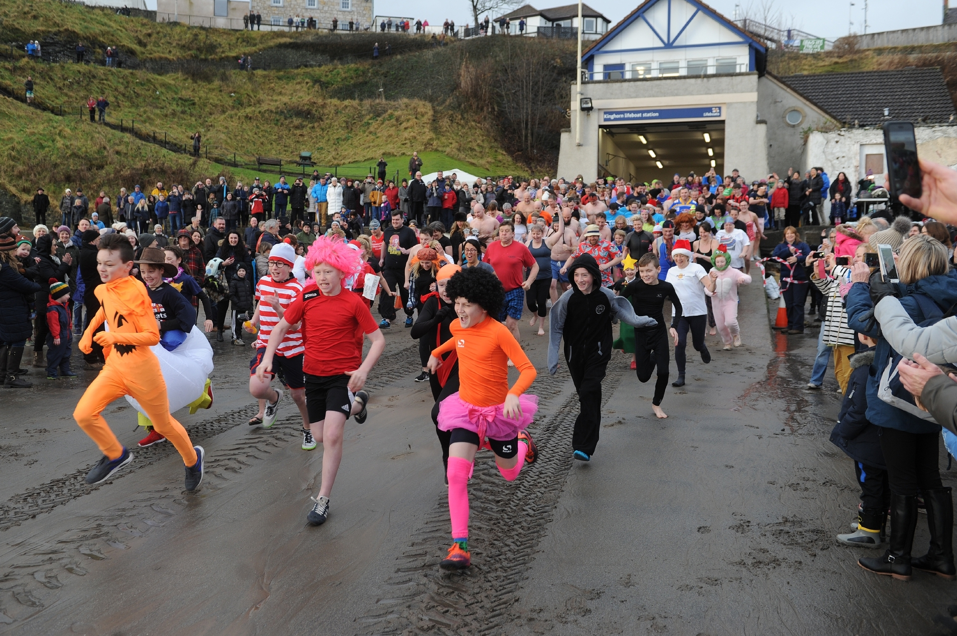 Some of the intrepid bathers run to the water.