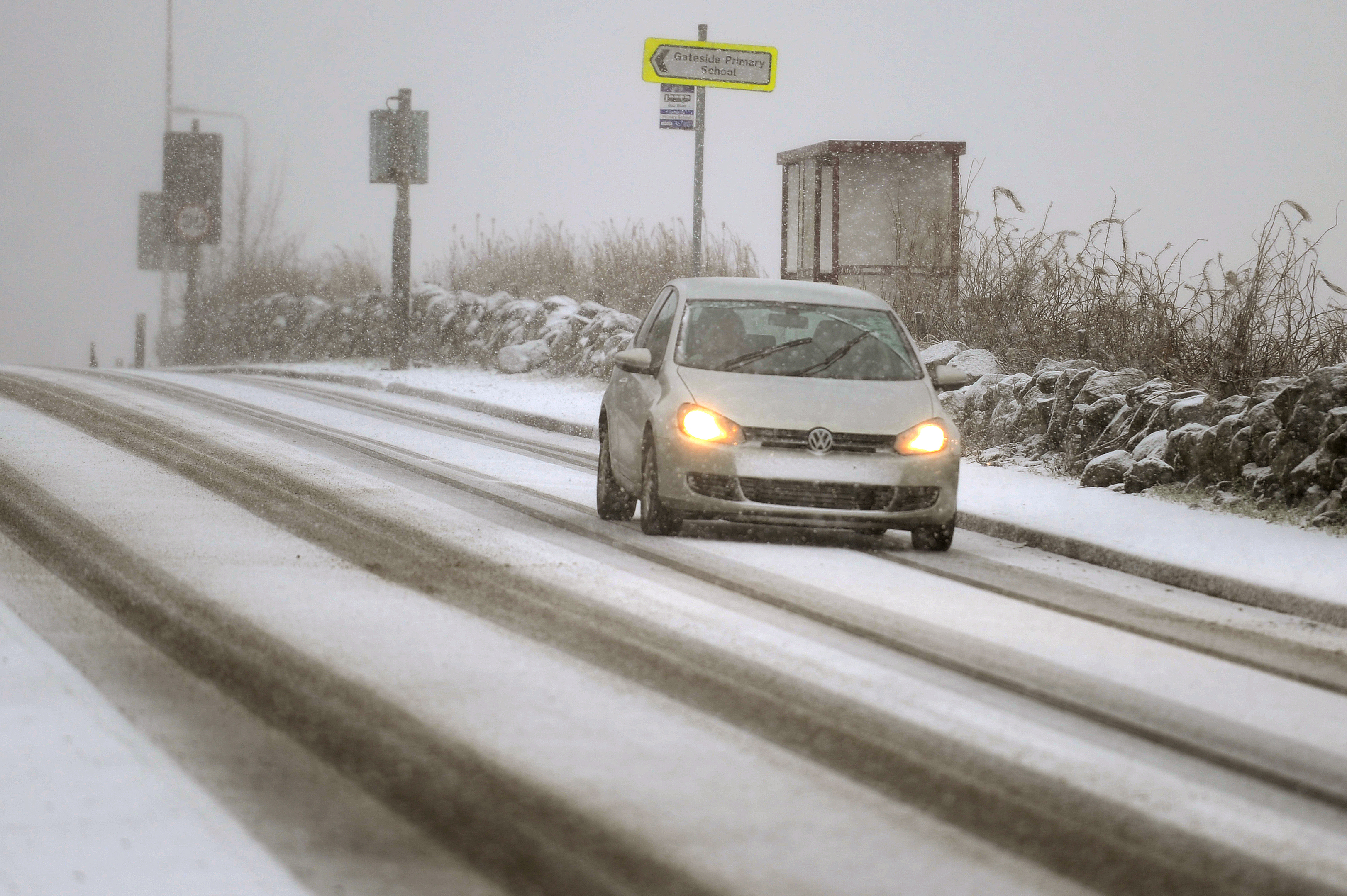 A car makes its way through the snow in Main Road, Gateside.