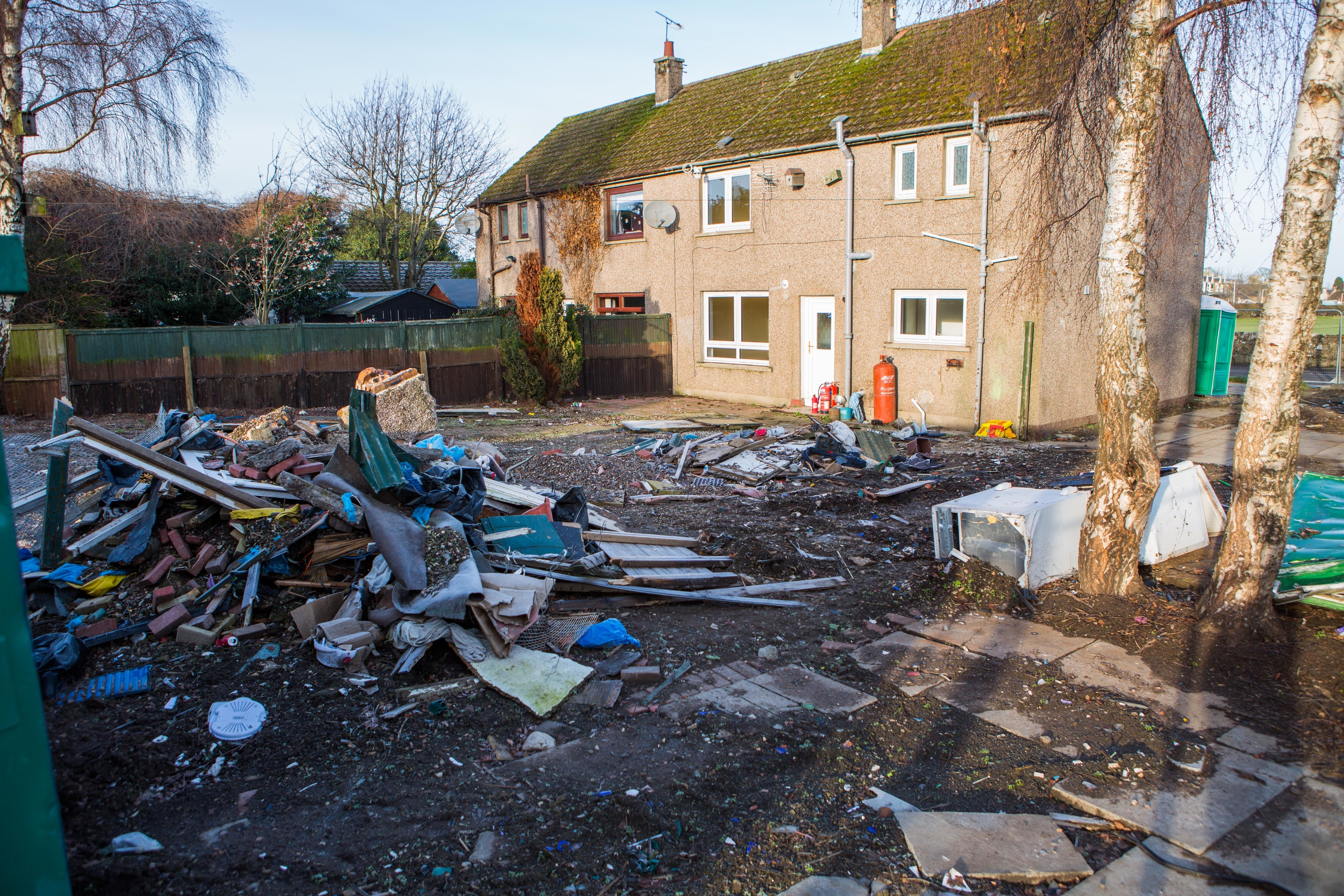Old fridges, skips, and general waste in a garden causing an eyesore
