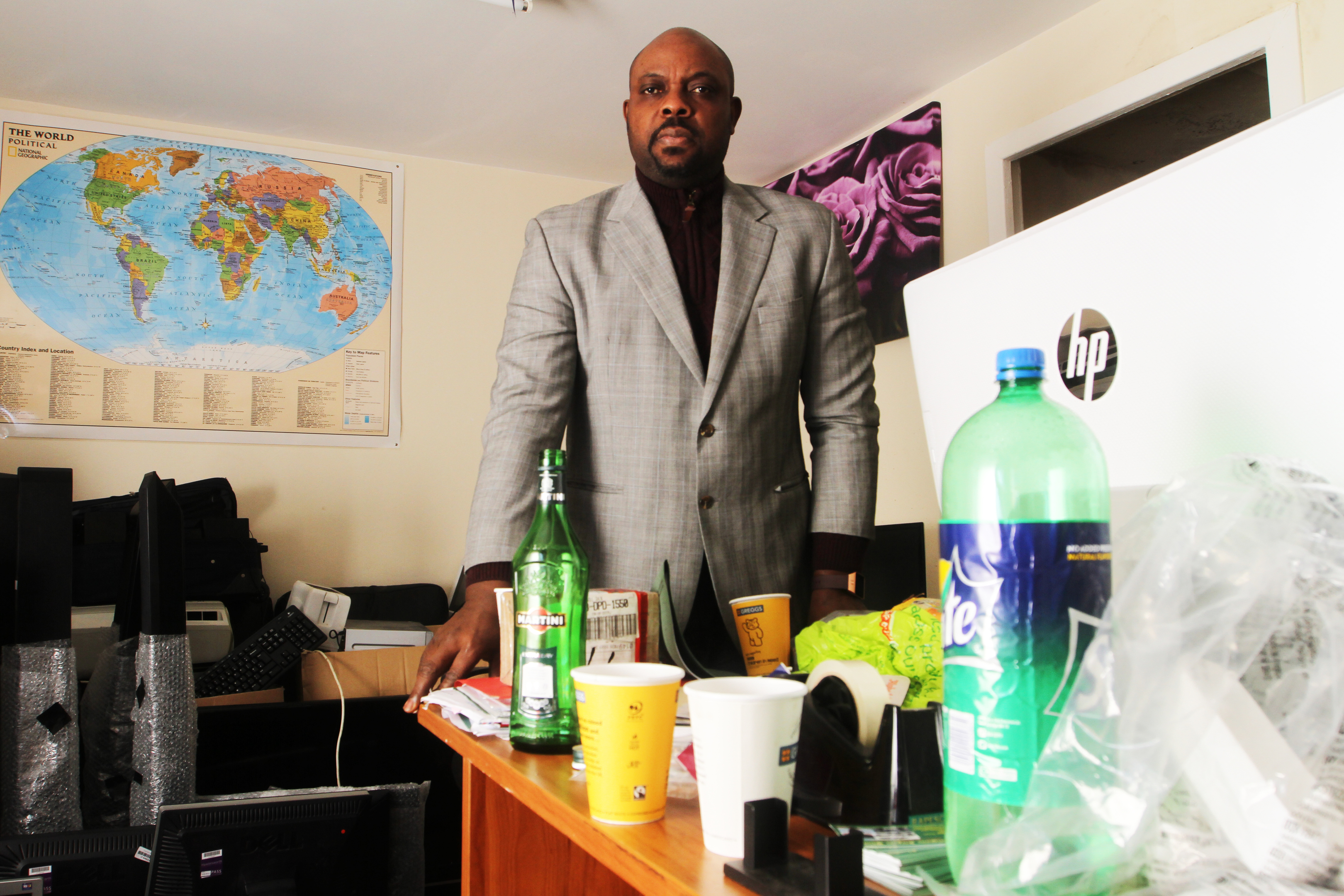 Oluwafani Oki in his Hilltown office with one of the drink bottles left behind by thieves visible on the desk.