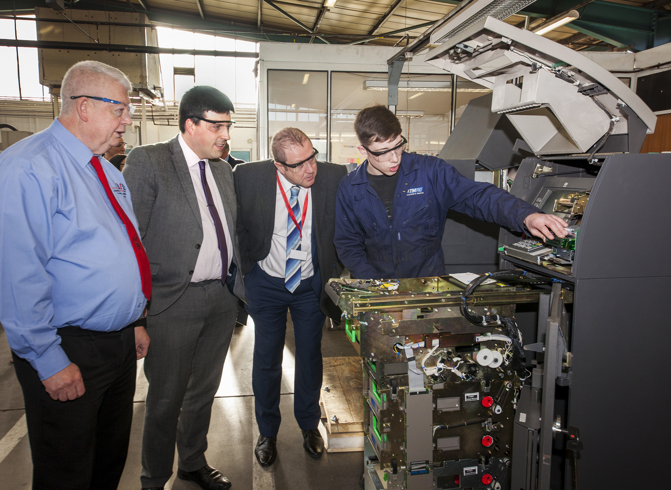 General manager Gary Talbot, Jamie Hepburn and Graeme Dey watch apprentice Flynn Suggett working on an ATM.