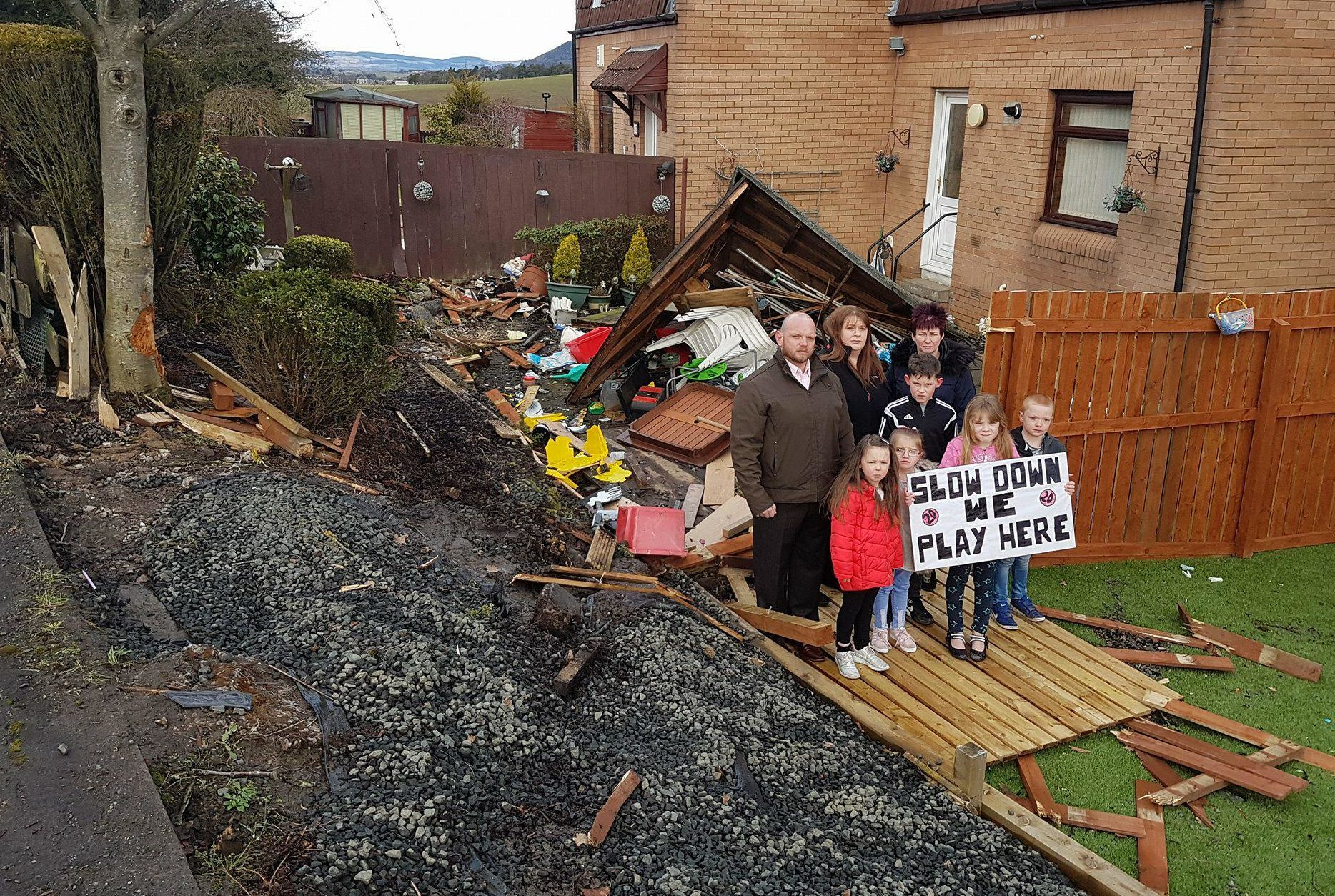 Councillor Darren Watt along with some of the families and local children living in fear, right beside the damage.